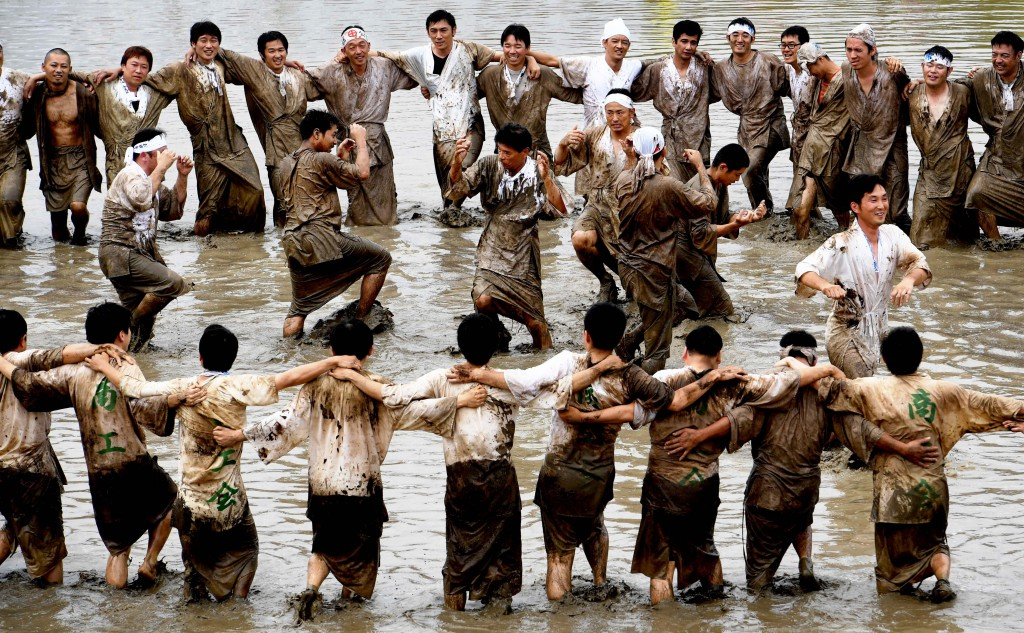 Young men dancing, singing and mixing mud using their feet in order to pray for huge harvest(in Hioki-shi, Kagoshima Prefecture)