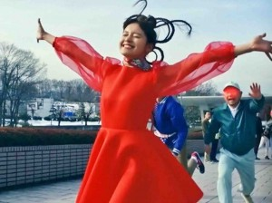 """A screen shot from the film """"Red Silk of Fate – Tamaki's Crush"""" shows a woman wearing red dress made from genetically modified silk spreading her arms.(Courtesy of Sputniko!)"""