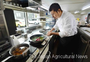Chef Motoshige Shimbo cooks dishes on the first floor of a double decker bus while it is making a stop during a tour.