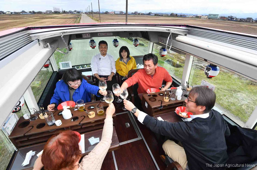 Tourists enjoy dining on the second floor of an open top double decker bus in the city of Niigata