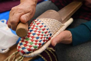 A woman shapes a slipper using a wooden mold and a rolling pin.