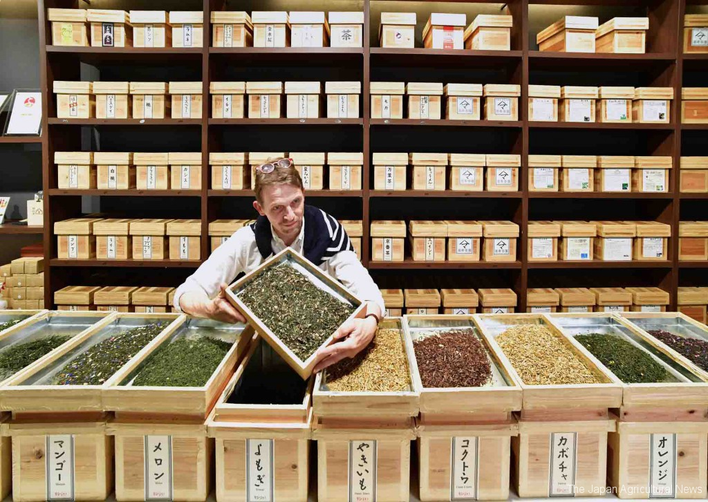 Shop owner of Ocharaka, Stephane, checking the flavor of his products in front of the large shelf of tea boxes (in Nihonbashi, Tokyo)