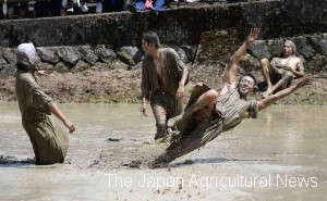 "Young local villagers performing ""Aze-mame-ue"" covered in mud"