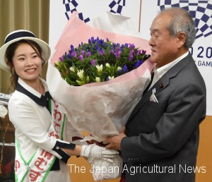 Suzuki, the minister in charge of the 2020 Tokyo Olympics and Paralympics Games, receiving a gentian bouquet from a campaign model of Iwate agricultural products. (in Kasumigaseki, Tokyo)