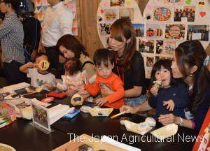 Children eat onigiri at an event held by TABLE FOR TWO on Oct. 5 to kick off a campaign to post onigiri photos on SNS and provide school meals for children in need.