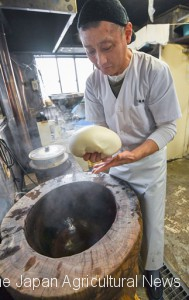 Shigeo Suzuki (61), an owner of Daifukuya founded in 1912, uses a mortar handed down by a local farmer.