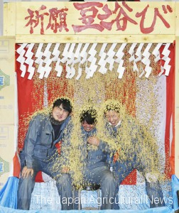 JA youth group members wished good harvest in 2018 by having soybeans poured over them at Kigan Mameabi section.