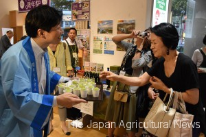 Okayama Goveror Ryuta Ibarakgi offered locally grown grapes to consumers at a Tokyo outlet.