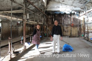 Shoichi Narita (right) and his wife Hiroko stand in an empty barn at their farm in Nemuro, Hokkaido.