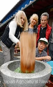 A tourist pounds steamed rice in front of a farm in Otsu, Shiga Prefecture.