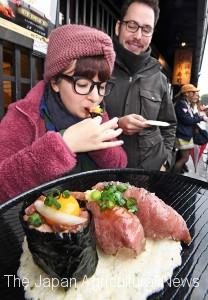 A Mexican tourist tastes wagyu sushi in Takayama, Gifu Prefecture.