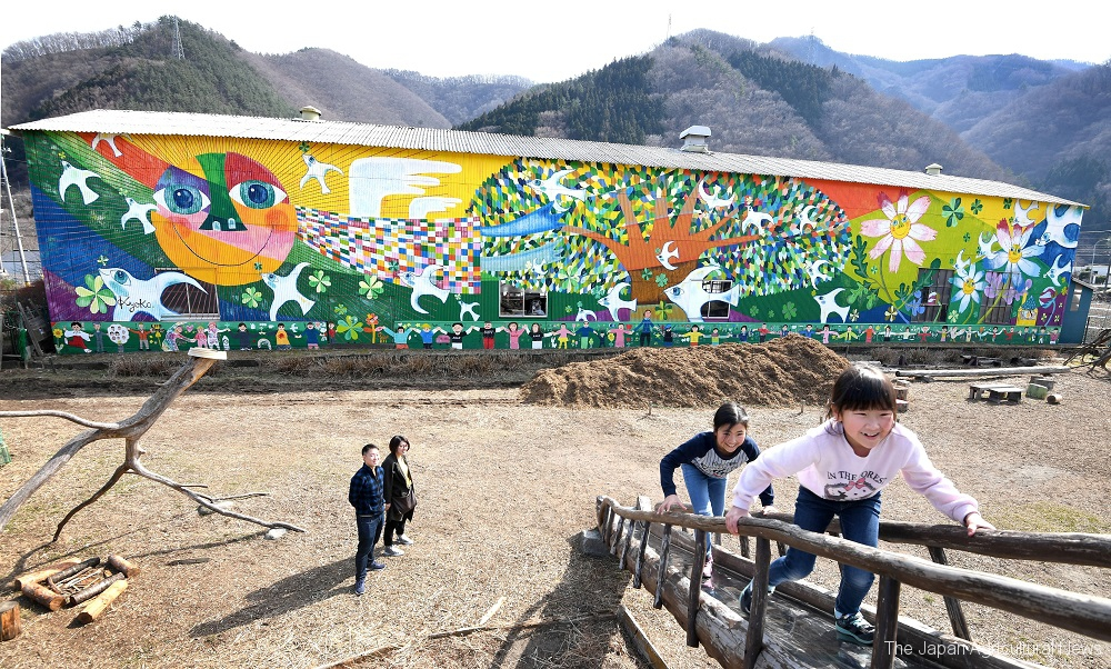 """The mural of hope"" in the park created at a quake-hit farmland. Colorful plants and animals in vivid and bright colors watch over the children playing in the park."