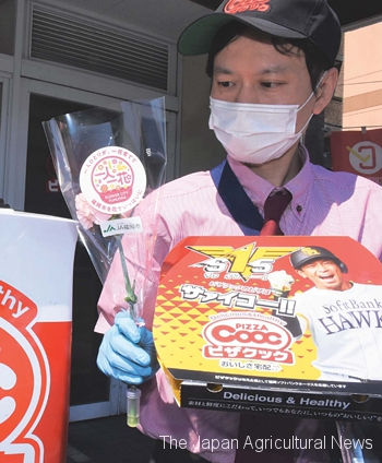 Pizza Cooc staff delivering freshly cooked pizza with a large carnation (on April 24 in Fukuoka City)