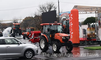 Mid-sized tractors with attachments and accessories making demonstration run in the show