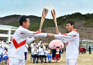 """Ryoji Sakuma (right) receiving the Olympic frame at a """"torch kiss"""" point and fist-bumping the previous torchbearer (left). His running course was in Katsurao Primary School, which is the old school for Ryoji, his father, and his grandfather. (in Katsurao Village, Fukushima Prefecture)"""