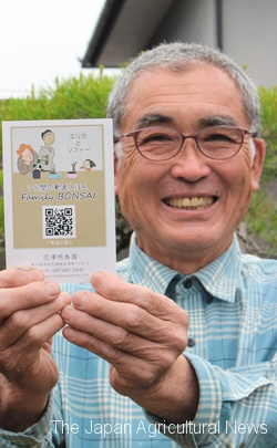Hanazawa with a postcard with a QR code link to the movie.